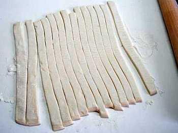 Тесто разморозить и раскатать в прямоугольный пласт толщиной 5 мм. Затем разрезать пласт на полоски шириной около 1 см.